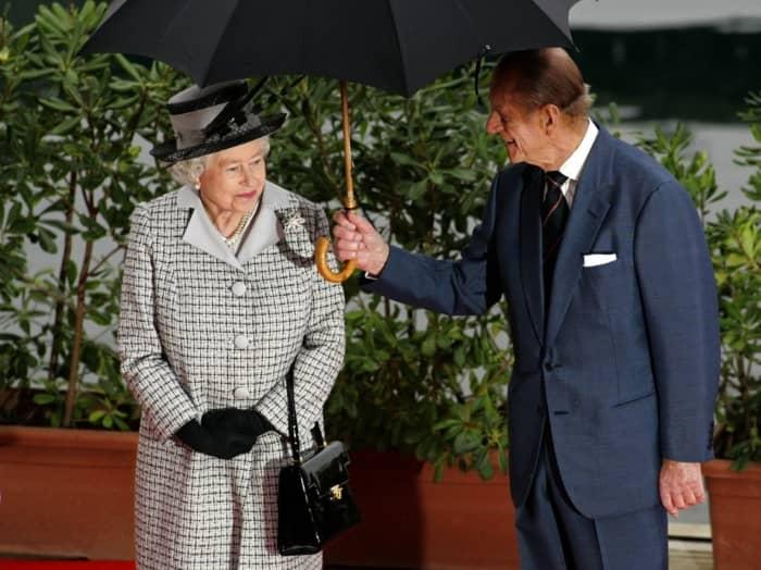 Принц Филипп держит зонтик для своей жены во время визита на Мальту.