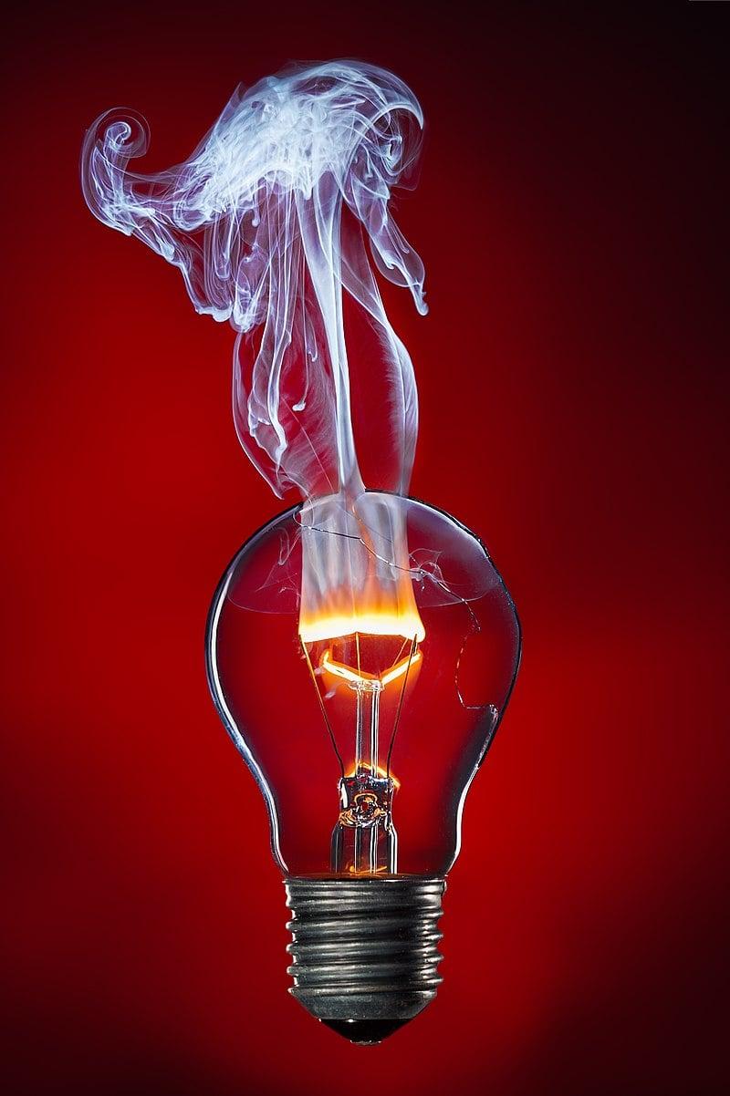 Лампочка с горящей и дымящейся вольфрамовой нитью