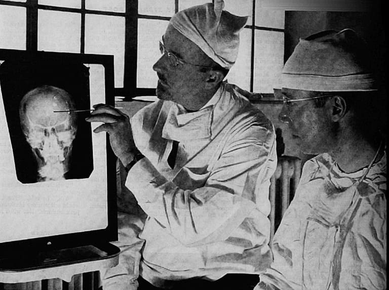 Доктор Уолтер Фриман (слева) и доктор Джеймс В. Уоттс изучают рентгеновский снимок перед психохирургической операцией.
