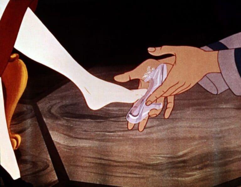 Прекрасный принц кладет Золушке стеклянную туфлю на ногу.
